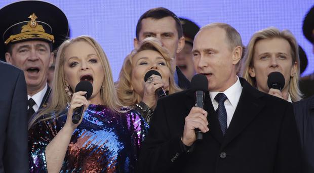 Russian president Vladimir Putin sings the national anthem at a rally marking the one-year anniversary of the annexation of Ukraine's Crimea peninsula (AP)