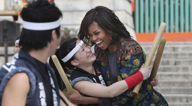 US First Lady Michelle Obama hugs a member of the Akutagawa High School Taiko Club (AP)