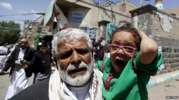 A man runs with a child from the bomb scene at the Badr and al-Hashoosh mosques