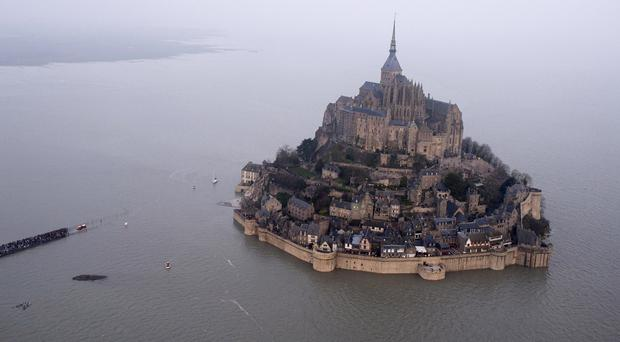 A high tide submerges a narrow causeway leading to Mont Saint-Michel (AP)