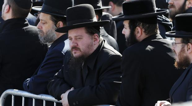 Mourners gather during for the funeral of the seven siblings killed in a house fire (AP)