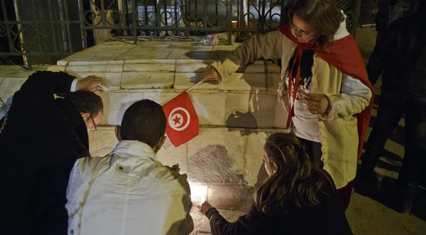 Tunisians light candles at the entrance gate of the National Bardo Museum where scores of people were killed after gunmen staged an attack (AP)