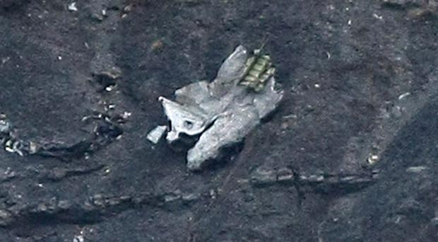 A piece of the crashed Germanwings passenger jet lies on the mountainside near Seyne les Alpes (AP)