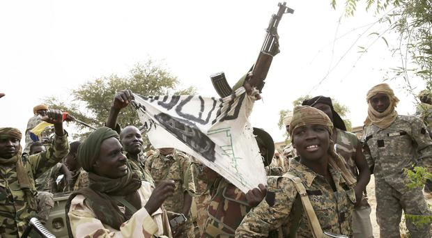 Chadian soldiers display a Boko Haram flag for the benefit of the press in the Nigerian city of Damasak (AP)