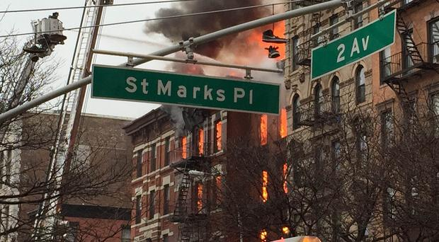 New York City firefighters work the scene of a large fire and a partial building collapse in the East Village neighbourhood of New York (AP)