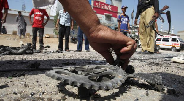 A Pakistani investigator collects evidence at the site of the bombing in Karachi. (AP)