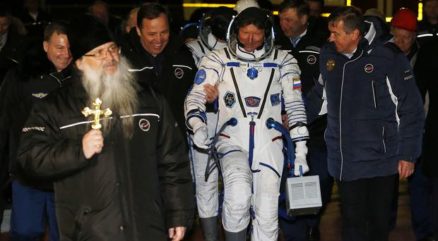 An Orthodox priest accompanies astronaut Scott Kelly and Russian cosmonauts Gennady Padalka and Mikhail Korniyenko to the launch of Soyuz-FG rocket (AP)