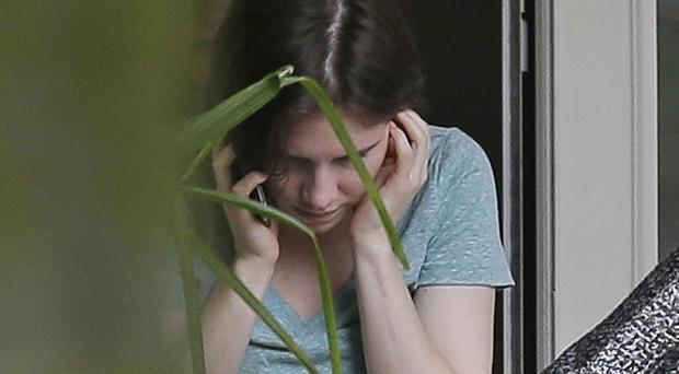 Amanda Knox talks on the phone in the garden of her mother's house after being acquitted by Italy's highest court (AP)