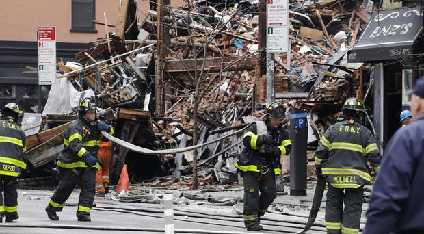 Firefighters work at the site of the explosion and fire in the East Village neighbourhood of New York, where at least two people are unaccounted for (AP)