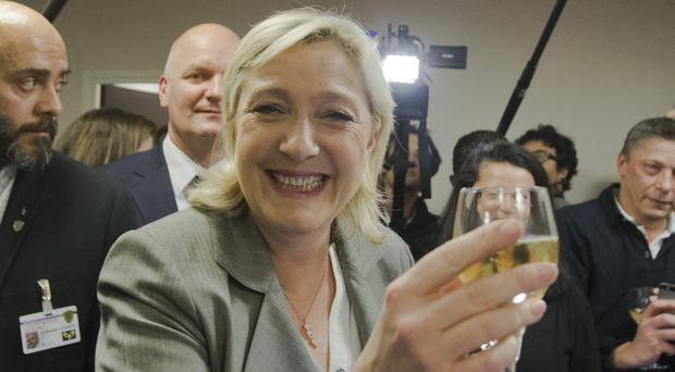 French far-right National Front Party leader, Marine Le Pen, smiles after a news conference at party headquarters (AP)