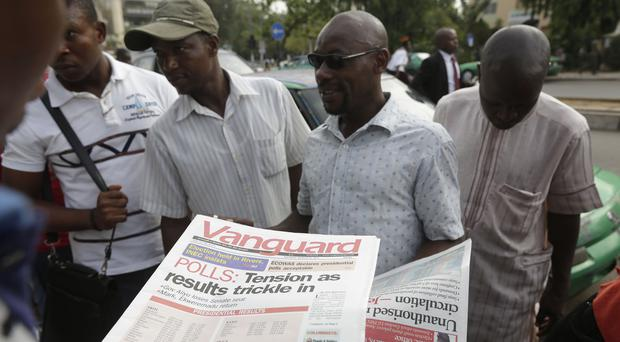 People in Nigeria read today's newspapers as they await the presidential election results (AP)