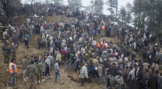 Kashmiri villagers and officials search for bodies of victims following landslides due to heavy rain in Laden, about 28 miles) west of Srinagar (AP)