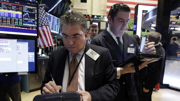 Trader John Bishop, left, works on the floor of the New York Stock Exchange (AP)