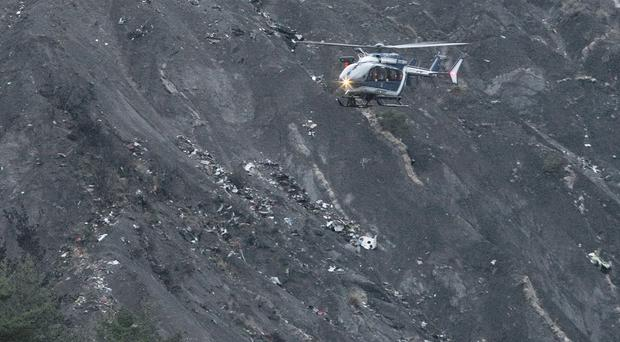 A rescue helicopter flies over debris of the Germanwings passenger jet, scattered on the mountain side, near Seyne les Alpes, France (AP)