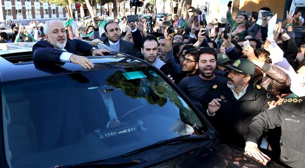 Mohammad Javad Zarif waves to the crowds on his arrival back from the Lausanne talks (AP)