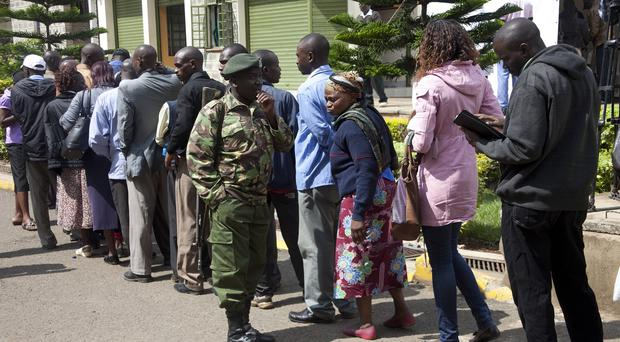 An army officer stands guard as relatives wait to view the bodies of loved ones who were killed during an attack on a university in Kenya (AP)