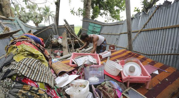 A Bangladeshi man tries to salvage his belongings after tropical storms damaged houses in the Gabtoli area of the northern Bogra district (AP)
