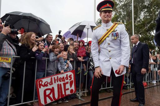 Prince Harry reacts after shaking hands with children holding up a sign reading 'Red Heads RULE!' during a visit to the Australian War Memorial in Canberra yesterday