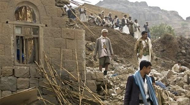 Yemenis stand amid the rubble of houses destroyed by Saudi-led airstrikes in a village near Sanaa (AP)