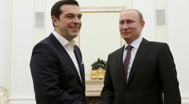 Greek prime minister Alexis Tsipras shakes hands with Russian president Vladimir Putin in Moscow's Kremlin (AP)