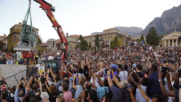 Students surround the statue of British colonialist Cecil John Rhodes as it is removed from the campus at Cape Town University (AP)
