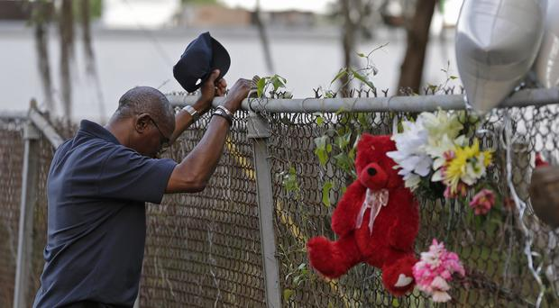Jerome Flood, of James Island, South Carolina, pauses for a moment at the scene of the killing of Walter Scott in North Charleston (AP)