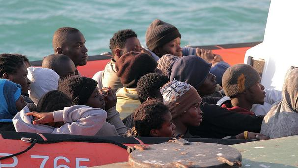 Migrants on a coastguard boat arrive at Porto Empedocle harbour in Sicily. (AP)