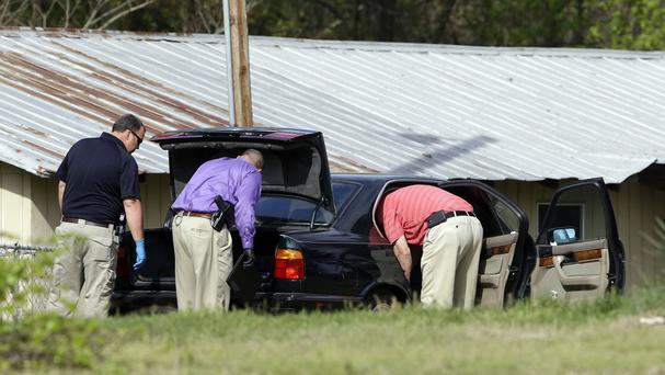 Authorities search a vehicle outside the home of shooting suspect Kenneth Stancil. (AP)