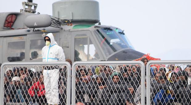 Rescued migrants wait to disembark from an Italian Navy vessel in the harbour of Reggio Calabria, southern Italy. (AP)