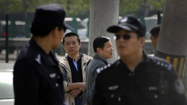 Chinese policemen stand guard near the Beijing No. 3 Intermediate Court (AP)