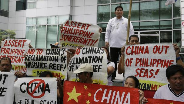 Protesters display placards during a rally at a Chinese consulate in the Philippines against Beijing's land reclamation activities on disputed territory in the South China Sea (AP)