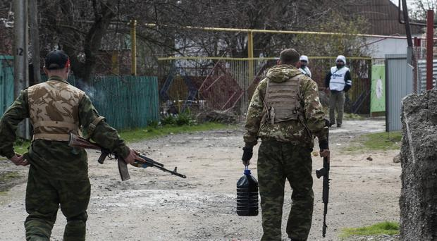 Pro-Russian separatists walk in a street patrolled by OSCE observers in eastern Ukraine (AP)
