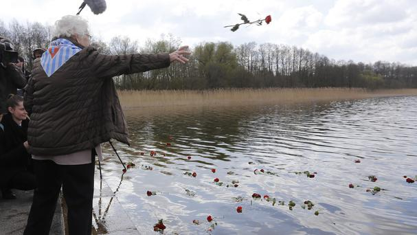 Flowers float in a lake after a commemoration event at the former Nazi concentration camp Ravensbrueck in Fuerstenberg, Germany (AP)