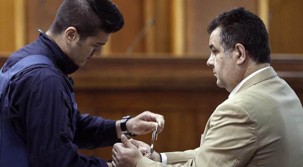 A police officer removes handcuffs from a suspect at the start of the trial. (AP)