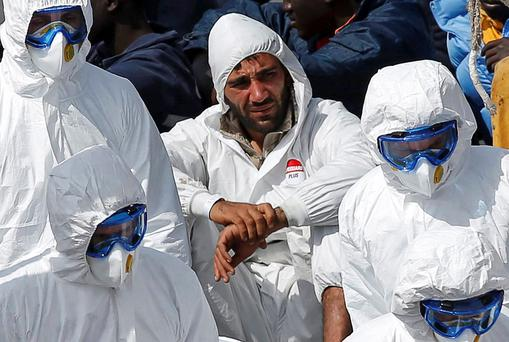A Tunisian survivor of the weekend's migrant disaster is taken to safety in Italy yesterday