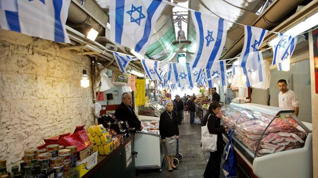 Israelis stand in the market in Jerusalem as they observe a two minutes' silence to mark the country's annual Memorial Day. (AP)