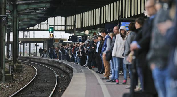 Commuters queue for rare trains during rush hour and train drivers' strike at a main railway station in Duisburg, Germany (AP)