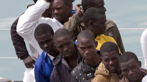 Migrants wait to disembark from the Italian Coast Guard ship Fiorillo, at Catania harbour, Sicily (AP)