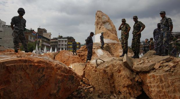 Police inspect what remains of Kathmandu's landmark Bhimsen tower after it was damaged in the earthquake (AP)
