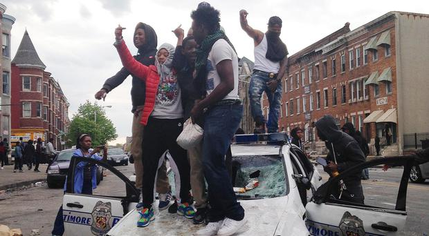 People stand on a Baltimore police car during unrest following the funeral of Freddie Gray (AP)