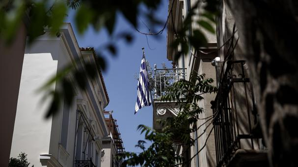 A Greek flag is seen on a balcony in Athens, as the country's prime Minister said a bailout deal was close (AP)