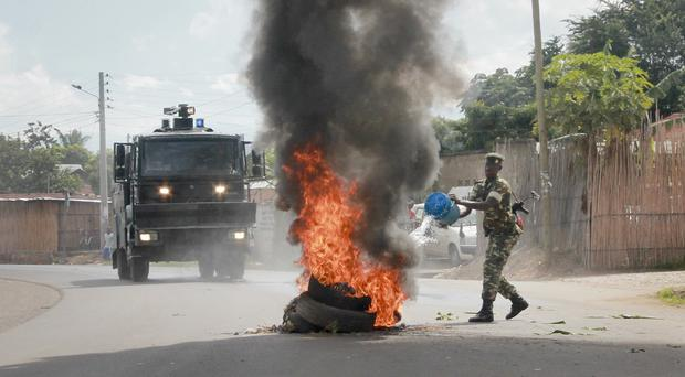 A Burundian army soldier pours water on a burning-tyre roadblock erected by opposition protesters in the capital Bujumbura (AP)