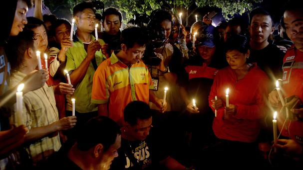 People hold candles to pray for death-row prisoners at Wijayapura port in Cilacap, Indonesia (AP)