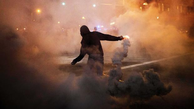 A protester throws a tear gas canister back at riot police in Baltimore (AP)