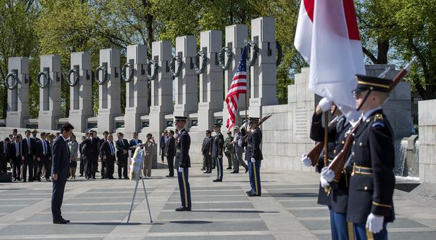 Japanese prime minister Shinzo Abe takes part in a wreath-laying ceremony at the National World War Two Memorial in Washington (AP)