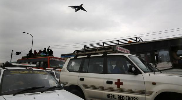 Buses loaded with Nepalese people leave Kathmandu as a relief cargo plane flies overhead (AP)