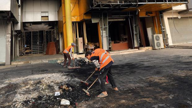 Workers clean up debris after a previous car bomb explosion in Baghdad (AP)