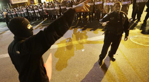 A protester argues with a policeman as officers line up in riot gear in Baltimore (AP)