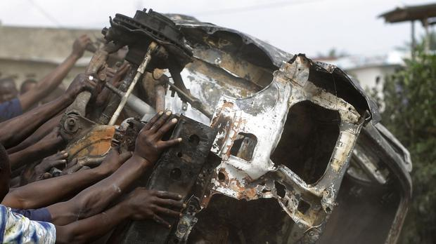 Demonstrators topple a burnt out car in the Musaga neighborhood of Bujumbura, Burundi. (AP)