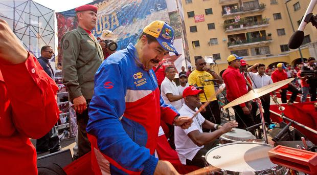 Venezuela's president Nicolas Maduro plays the drums as he arrives for a May Day rally in Caracas (AP)